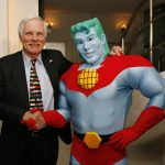 Ted Turner shaking hands with Captain Planet, a cartoon character he helped create and aired as a cartoon from 1990-1996.