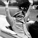 General Eisenhower extends hands to wave to the throng of people lining NYC's streets.